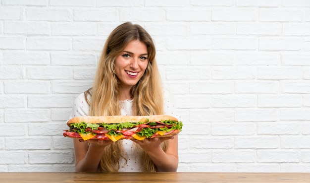 大きなサンドイッチを保持している幸せな若いブロンドの女性