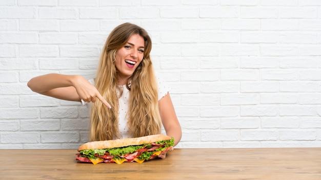 Счастливая молодая белокурая женщина держа большой сандвич