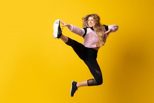 孤立した黄色の壁の上に踊り、ジャンプ都市バレリーナ