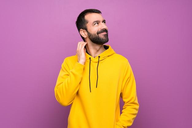 アイデアを考えて黄色のトレーナーとハンサムな男