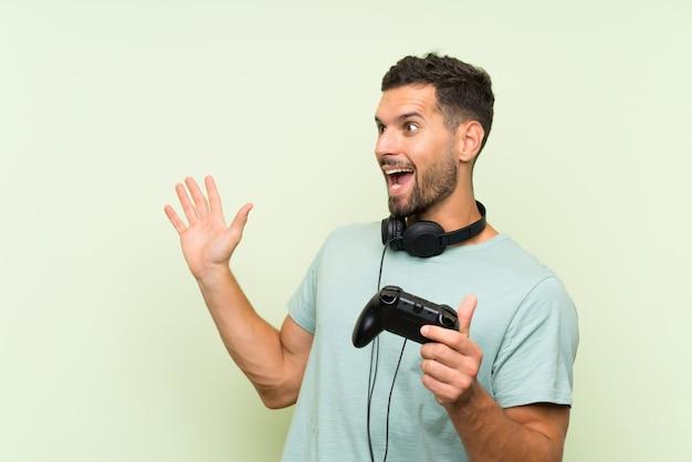 驚きの表情で孤立した緑の壁を越えてビデオゲームコントローラーで遊ぶ若いハンサムな男