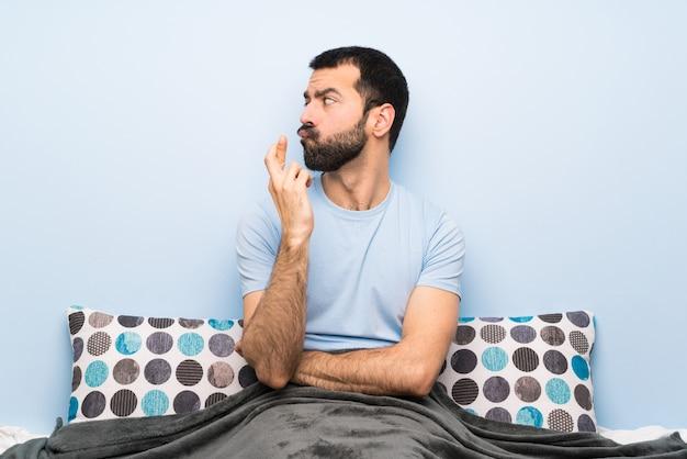 Мужчина в постели, скрестив пальцы и желая лучшего