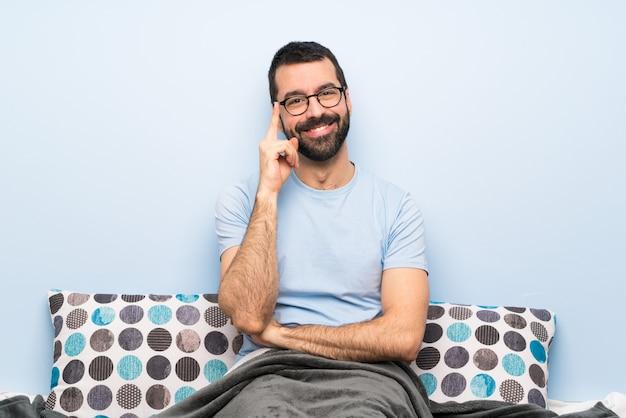 メガネと幸せなベッドの男