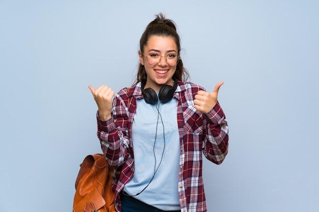 ジェスチャーと笑みを浮かべて親指で分離の青い壁の上のティーンエイジャーの学生の女の子