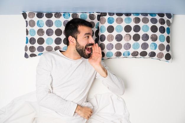Мужчина в постели на вид сверху кричит с широко открытым ртом к боковой