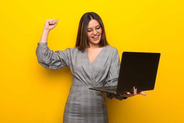 ラップトップと勝利を祝って黄色の壁の上の眼鏡を持つ若い女性