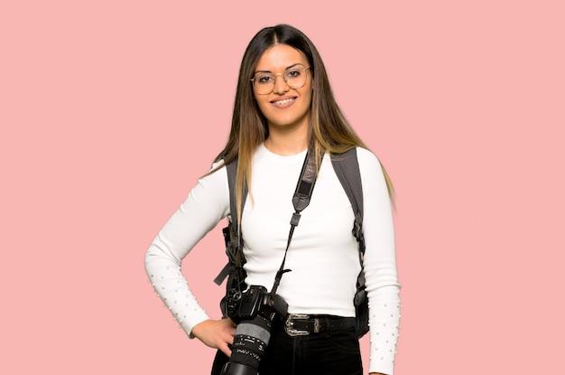 若い写真家の女性が腰に腕でポーズと分離のピンクの壁に笑みを浮かべて