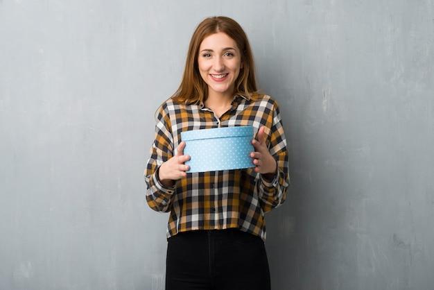 Молодая рыжая девушка над гранж-стеной удивлена, потому что ей дали подарок