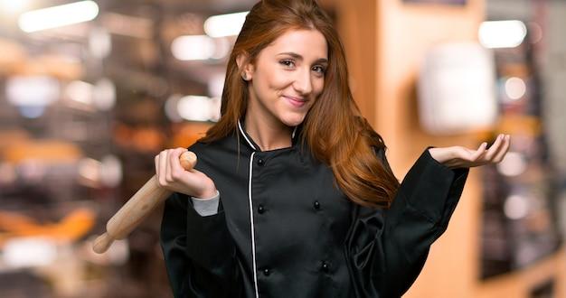 Молодая рыжая шеф-повар женщина, имея сомнения, поднимая руки и плечи в пекарне