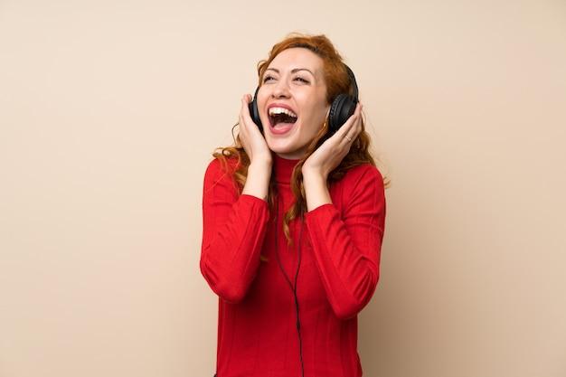 ヘッドフォンで音楽を聴くタートルネックのセーターと赤毛の女性