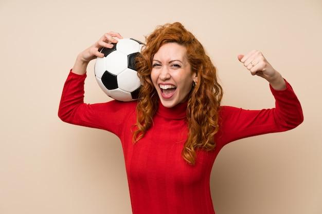 サッカーボールを保持しているタートルネックのセーターと赤毛の女性