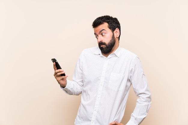 ひげを生やした携帯電話の疑いジェスチャー側を探して保持している若い男