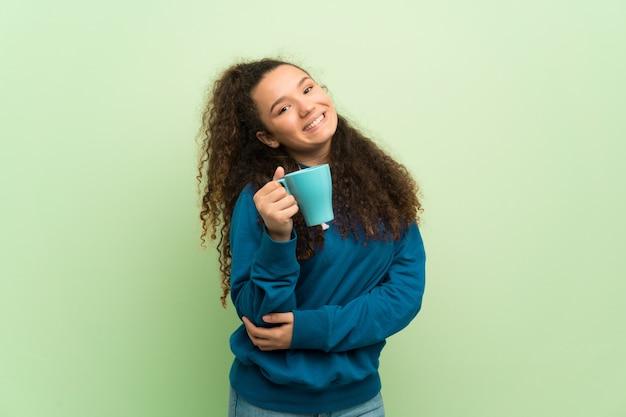 熱い一杯のコーヒーを保持している緑の壁の上のティーンエイジャーの女の子