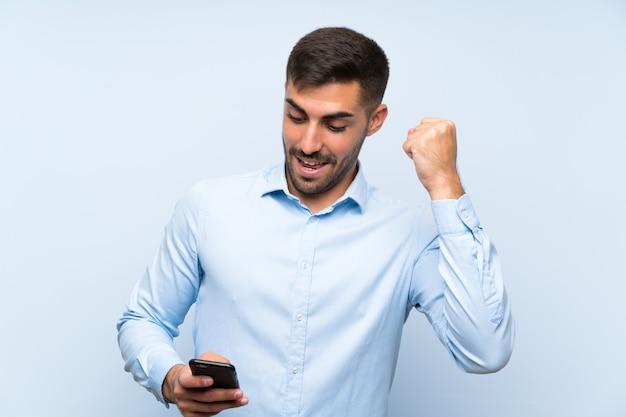 勝利を祝う分離の青い壁の上の彼の携帯電話で若いハンサムな男