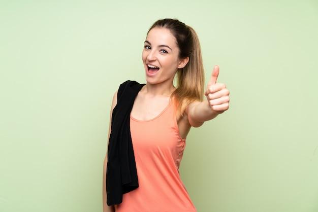 何か良いことが起こったので、親指で緑の壁の上の若いスポーツ女性