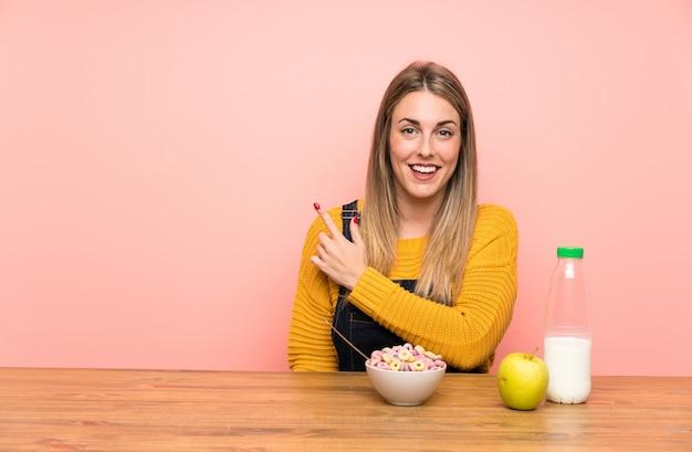側に指を指している穀物のボウルを持つ若い女性