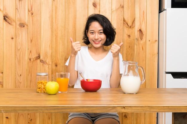 ジェスチャを親指を与える朝食牛乳を持つアジアの若い女性
