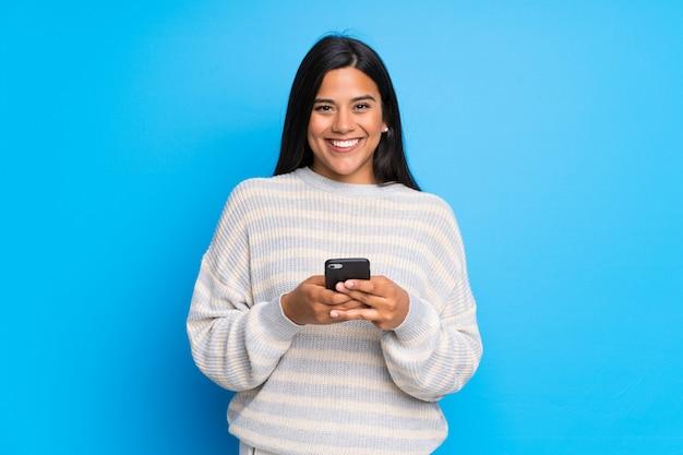 Молодая колумбийская девушка со свитером отправляет сообщение с мобильного