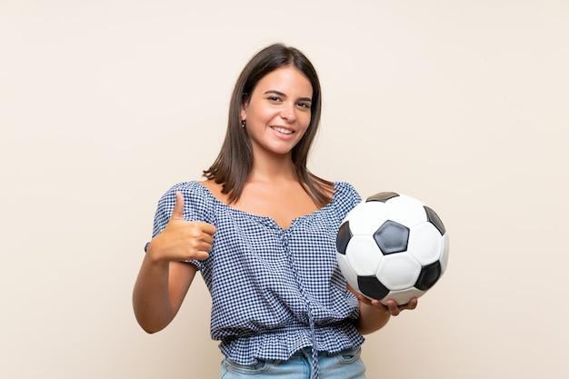サッカーボールを保持している孤立した壁の上の少女