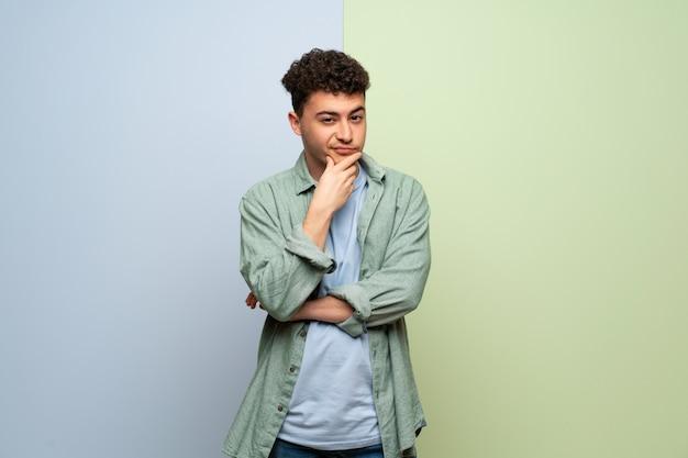 正面を向いた青と緑の壁の上の若い男