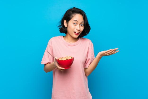 ショックを受けた表情で穀物のボウルを保持しているアジアの若い女性