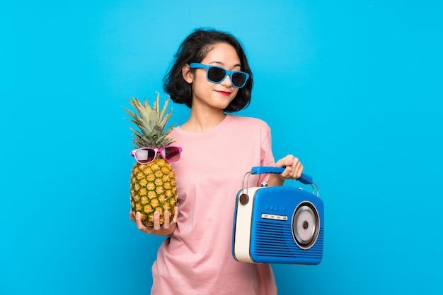 サングラスとラジオとパイナップルを保持している孤立した青い壁の上のアジアの若い女性