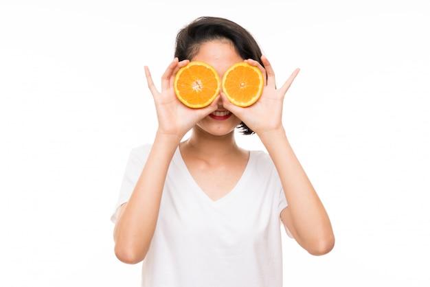 メガネとしてオレンジスライスを着てアジアの若い女性