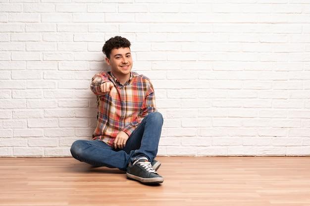 床に座っている若い男が自信を持って式であなたに指を指す