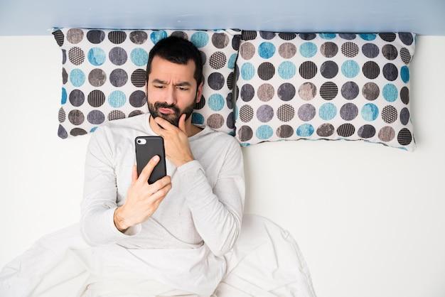 思考とメッセージを送信するトップビューでベッドの男