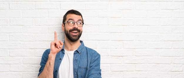 指を上向きのアイデアを考えて白いレンガの壁の上のひげを持つハンサムな男