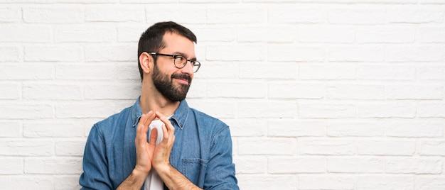何かをスキームの白いレンガの壁の上のひげを持つハンサムな男