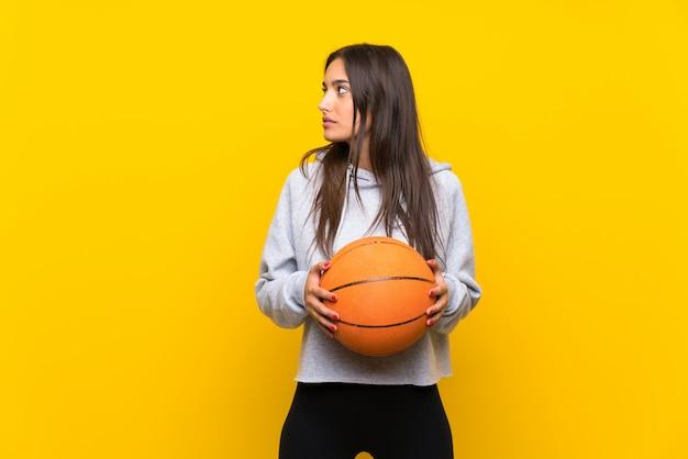 孤立した黄色の壁を越えてバスケットボールをする若い女性