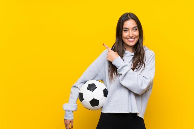 製品を提示する側を指している孤立した黄色の壁の上の若いフットボール選手女性