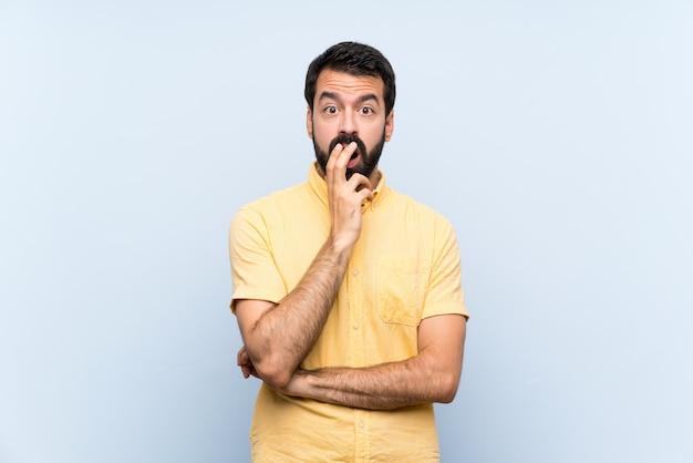 Молодой человек с бородой на изолированной синей стене удивлен и шокирован, глядя прямо