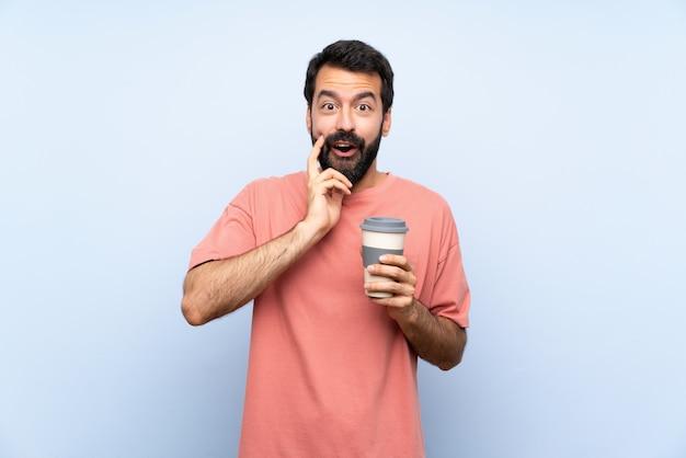 Молодой человек с бородой, держа прочь кофе над синей стеной с удивлением и шокирован выражением лица