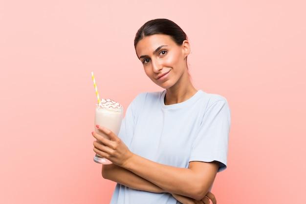 笑顔ながら見上げる孤立したピンクの壁にいちごのミルクセーキを持つ若い女性