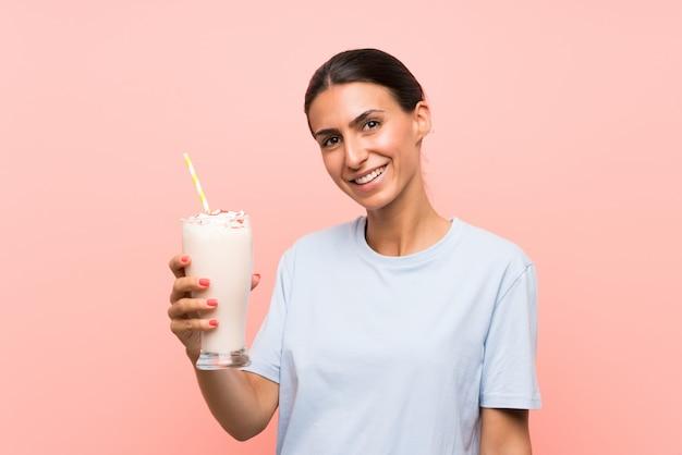孤立したピンクの壁の上のいちごのミルクセーキを持つ若い女性