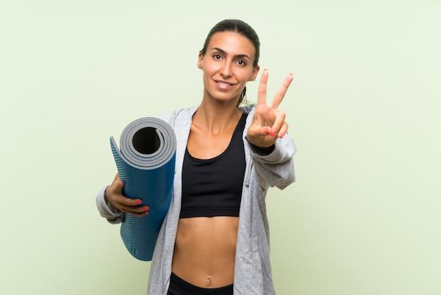 笑顔と勝利のサインを示す分離の緑の壁の上のマットを持つ若いスポーツ女性