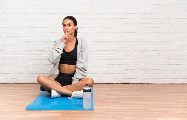 沈黙のジェスチャーをしてマットで床に座っている若いスポーツ女性