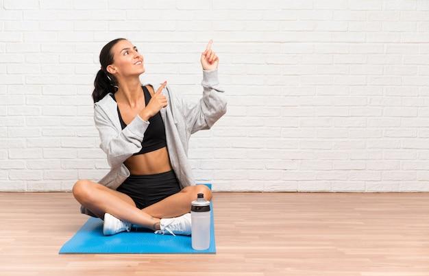 人差し指で素晴らしいマットを指しているマットで床に座っている若いスポーツ女性