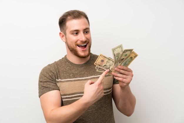 たくさんのお金を取って孤立した白い壁の上のハンサムな男