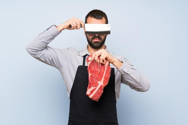 彼の目を覆っている生の肉を保持しているシェフ