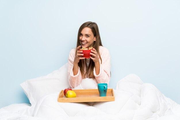 朝食のドレッシングガウンで幸せな若い女