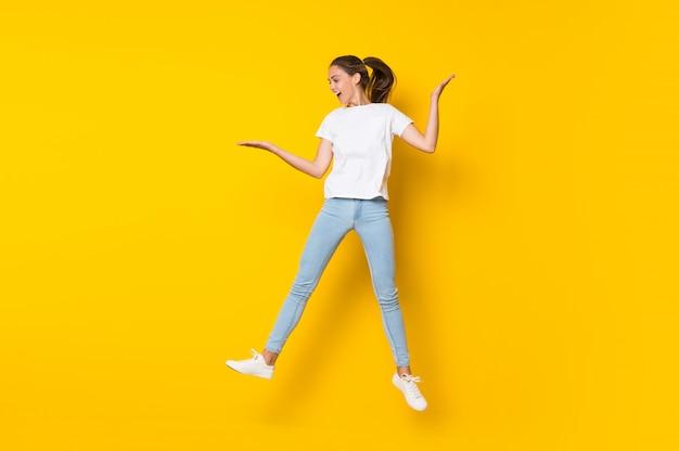 孤立した黄色の壁を飛び越えて若い女性