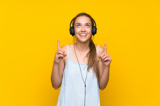 素晴らしいアイデアを指している孤立した黄色の壁で音楽を聴く若い女性