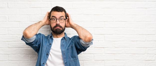 Красивый мужчина с бородой над белой кирпичной стеной расстроен и берет руки на голову