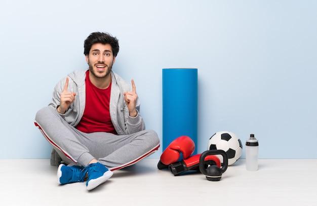 素晴らしいアイデアを指している床に座ってスポーツ男