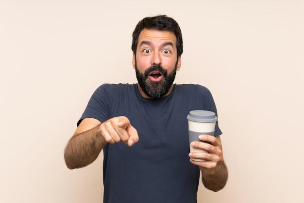 Человек с бородой, держа кофе удивлен и указывая спереди