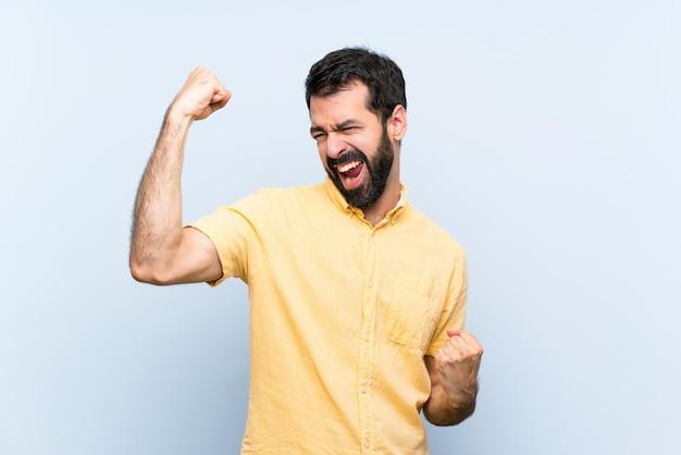勝利を祝う分離の青い壁の上のひげと若い男