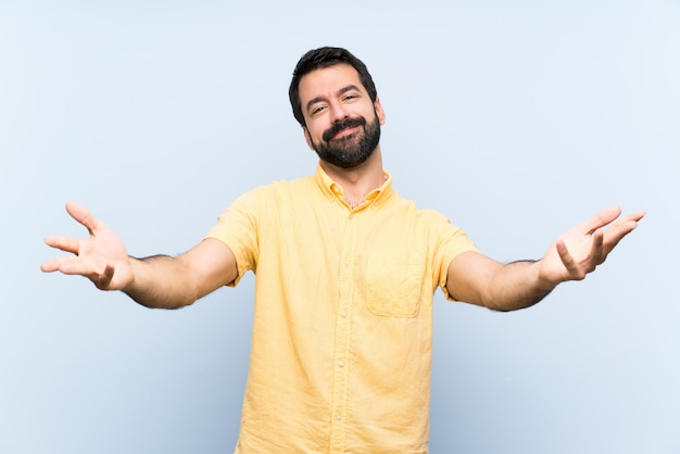 孤立した青い壁を提示し、手に来るように招待してひげを持つ若者